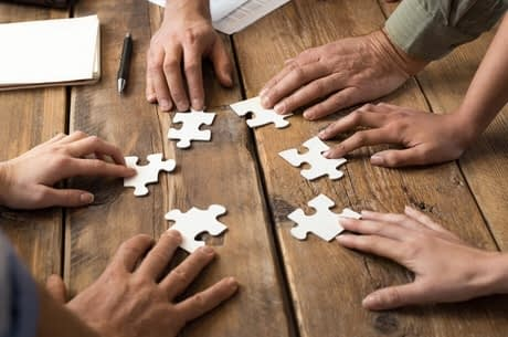 six hands each holding a blank puzzle piece on wood table