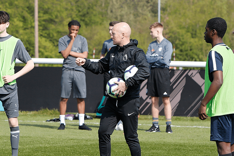 soccer coach holding soccer ball and talking to players